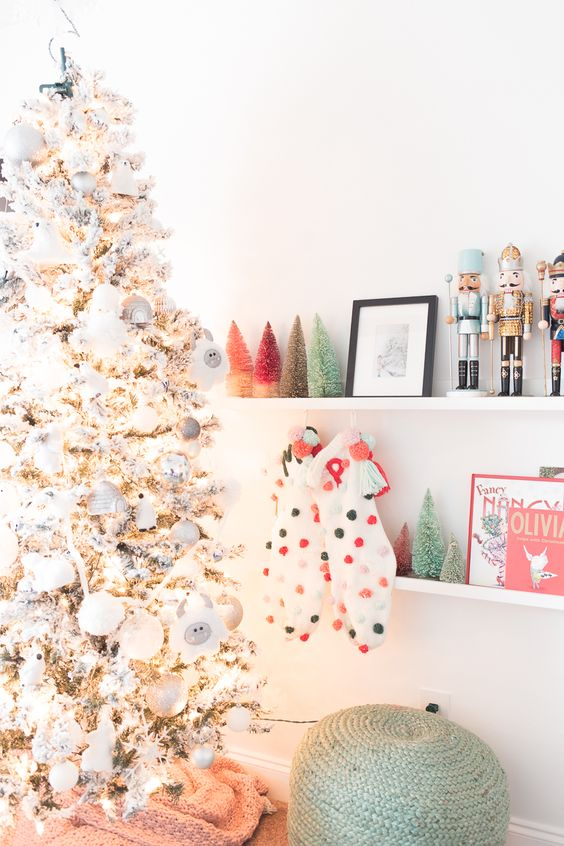 a flocked Christmas tree with white and silver ornaments, colorful pompom stockings and colorful tinsel Christmas trees on the shelf