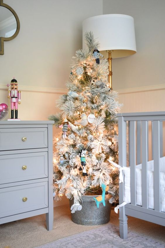 a flocked Christmas tree with lights and bvarious ornaments in a bucket to create a holiday feel in a farmhouse nursery