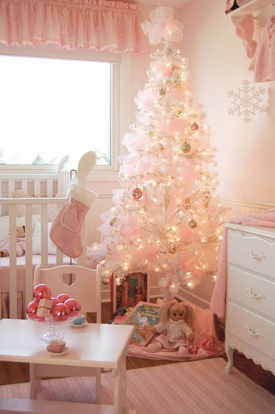 a white Christmas tree decorated with pastel ornaments, pink bows, a pink stocking and ornaments on the table for a little girl's room