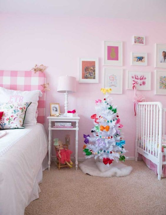 a white Christmas tree with colorful bows and bright pompom garlands will easily bring a festive feel to the space