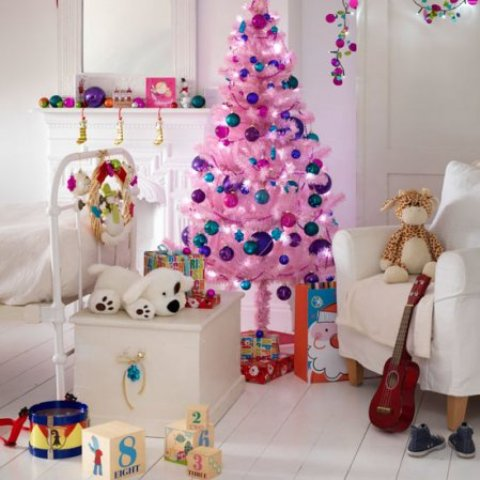 a white kids' room with bright Christmas decor - a bright pink Christmas tree with colorful ornaments, bright ornaments on the mantel and bright flowers hanging down from the ceiling