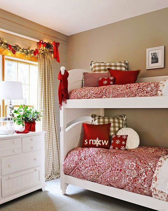 printed red and white bedding, a garland with bows, a scarf and decorative red vase with some greenery for a holiday touch