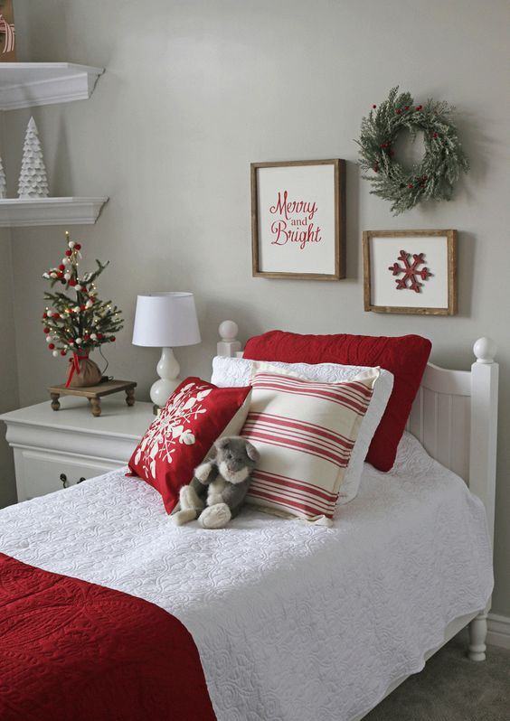 Christmas printed bedding and pillows, a tiny tabletop Christmas tree with gold, red and green Christmas ornaments, some art and a wreath