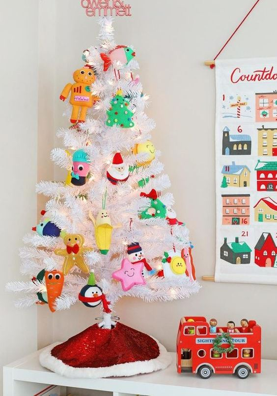 a white Christmas tree with lights and funny colorful ornaments is an easy and fun way to add a holiday feel to the room
