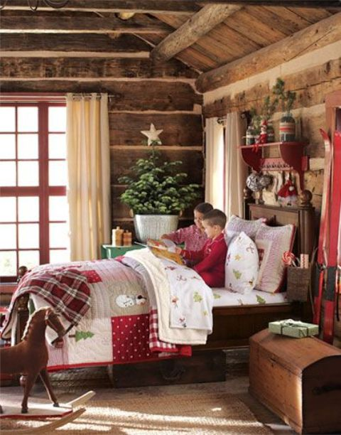 a rustic kids' room decorated for Christmas with bright bedding and blankets, a Christmas tree with a star topper and some branches over the bed