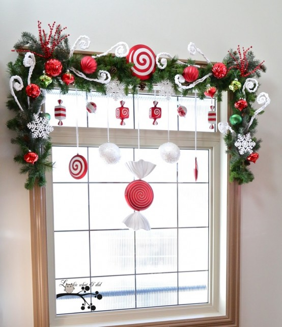 pretty and cute Christmas window decor with fir garlands, red and white ornaments, snowflakes and candies is a very cool idea for a kids' room