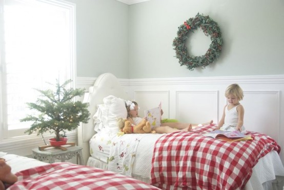 a wreath, a potted Christmas tree with lights and red plain bedding bring a holiday feel to this shared kids' room