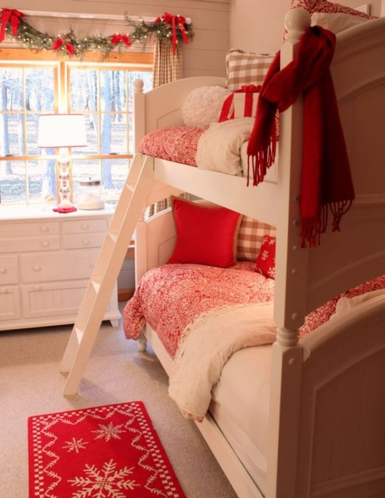 red and plaid festive bedding and a rug plus some garlands with red bows on the window for a cozy wintry feel in the space