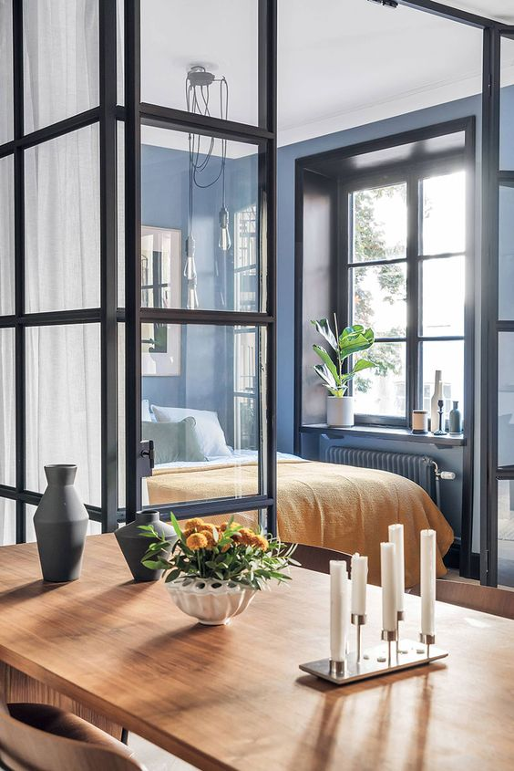 a modern bedroom with blue walls, a bed, some statement plants and vases and glass walls all over to maximize the daylight