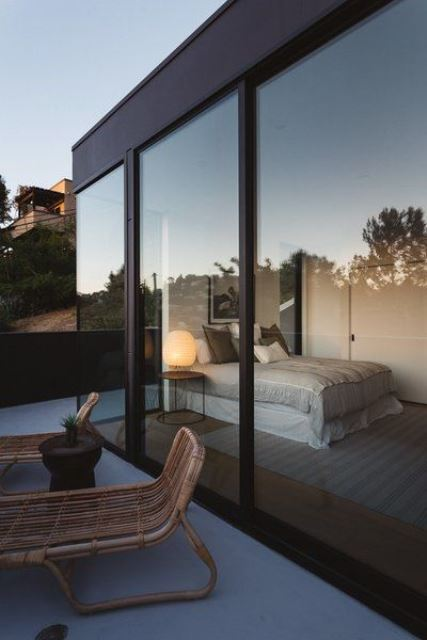 a simple contemporary bedroom with a bed, a nightstand with a lamp and glass walls plus an entrance to the terrace is very cool