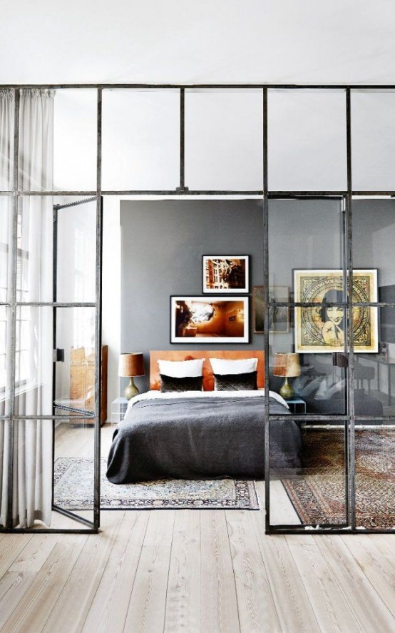 a stylish eclectic bedroom with a grey statement wall, a leather upholstered bed, nightstands and boho rugs plus a framed glass wall that divides the bedroom from the rest of the space