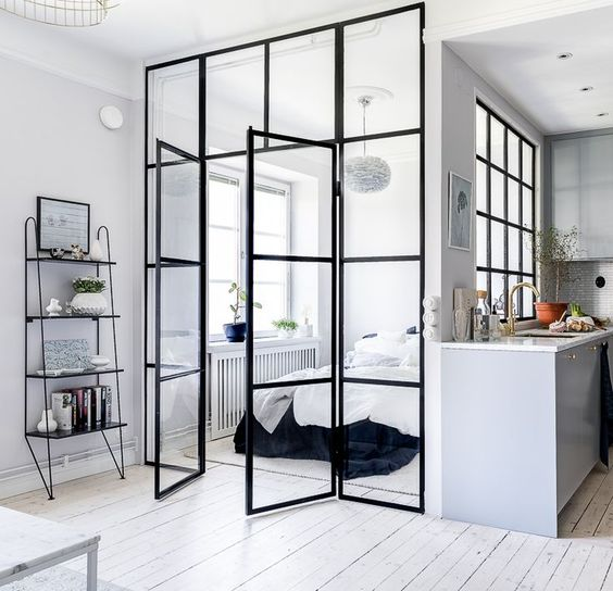 a monochromatic Scandinavian bedroom with a bed, a pendant lamp and stylish bedding clad in glass completely feels very airy and light-filled
