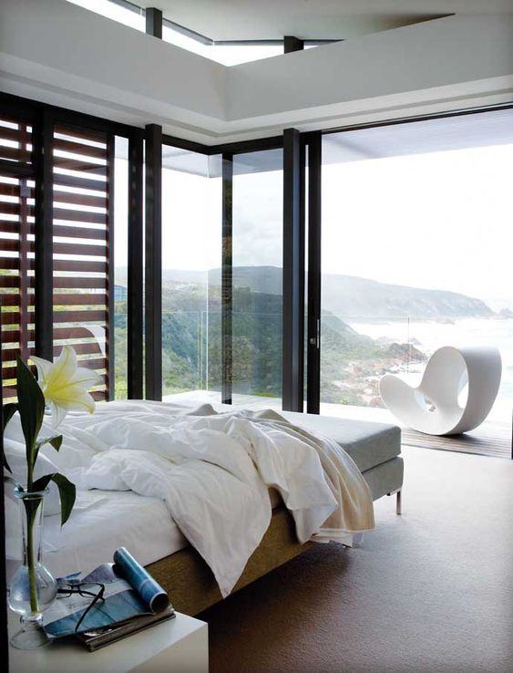 a lovely contemporary bedroom with a bed, a bench, nightstands, glass walls and a balcony plus amazing ocean views