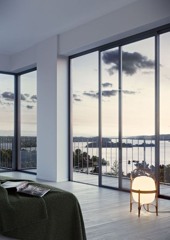 a minimalist bedroom with a bed, some lamps and gorgeous sea views through glass walls is a fantastic space to be