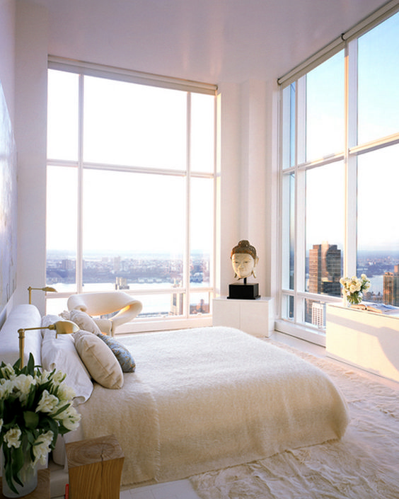 a stunning neutral bedroom with some cabinets, a bed, tree stumps, a bet chair and glass walls with the views of a big city