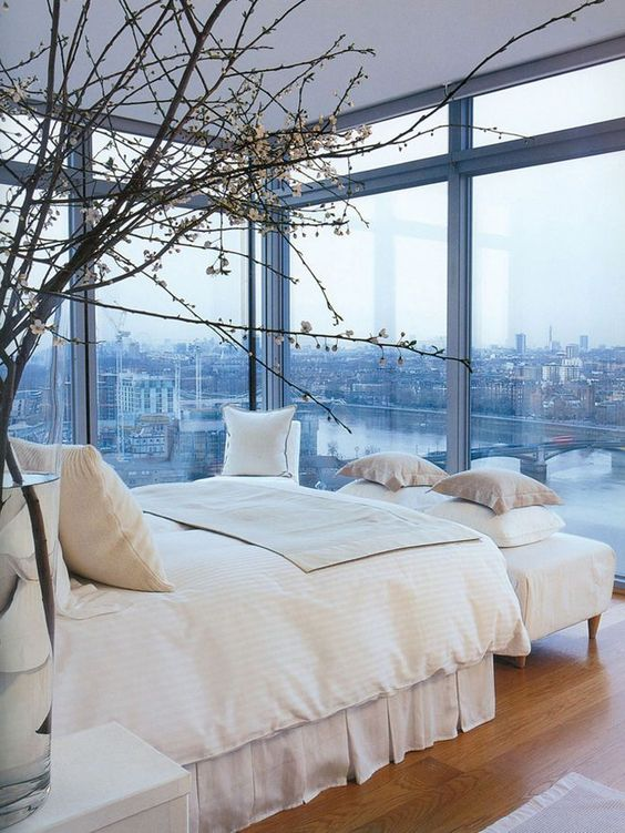 an elegant modern bedroom with a bed, an upholstered bench, some nightstands and glass walls to enjoy the views of the city