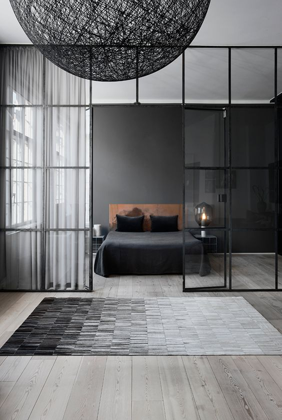 a moody Nordic bedroom with a black statement wall, a leather bed, nightstands and laps and a glass framed wall that separates it from the rest of the apartment
