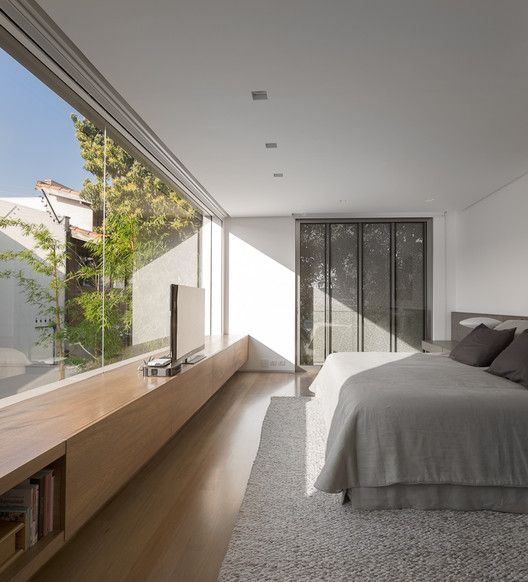 a minimalist bedroom with storage hidden in the wall, a bed, a sleek storage unit and a glass wall with a view of a private courtyard