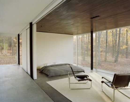 a minimalist bedroom with a mattress on the floor, some chairs and a glass wall with a forest view is veyr calming and peaceful