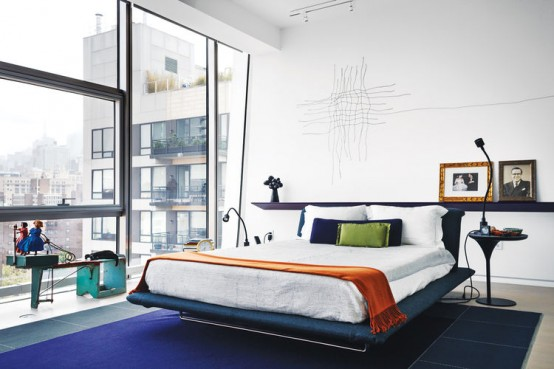 a contrasting modern bedroom with a navy rug, a navy upholstered bed, chic nightstands, table lamps and a glass wall with windows in it