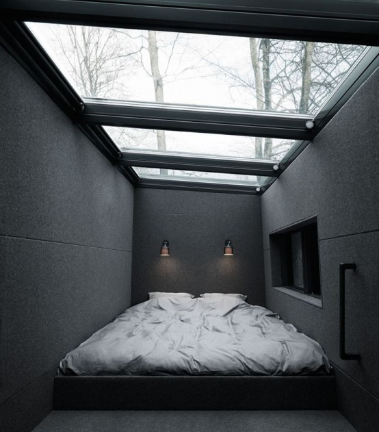 a moody dark bedroom with only a bed on the floor, some sconces, a niche and a glazed ceiling to mazximize daylight in here and look at the stars