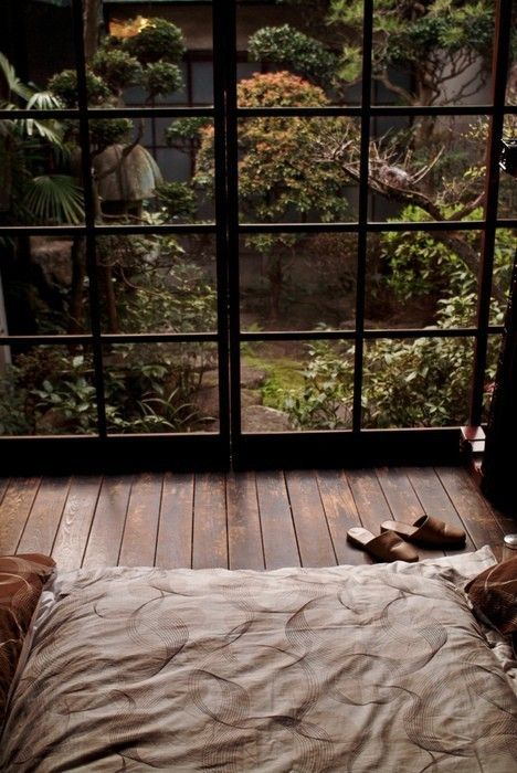 a simple and peaceful zen bedroom with a bed on the floor and a framed glass wall with a gorgeous view to a Japanese garden
