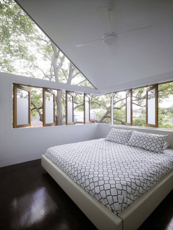 a peaceful and cozy bedroom with an upholstered bed and a gallery of windows plus a large skylight to maximize the daylight and enjoy fresh air