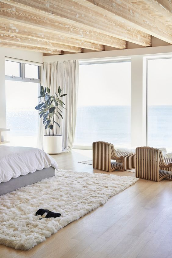 a cozy and stylish contemporary bedroom with catchy bent wooden loungers, a bed, a white fur rug and a statement plant plus sea views