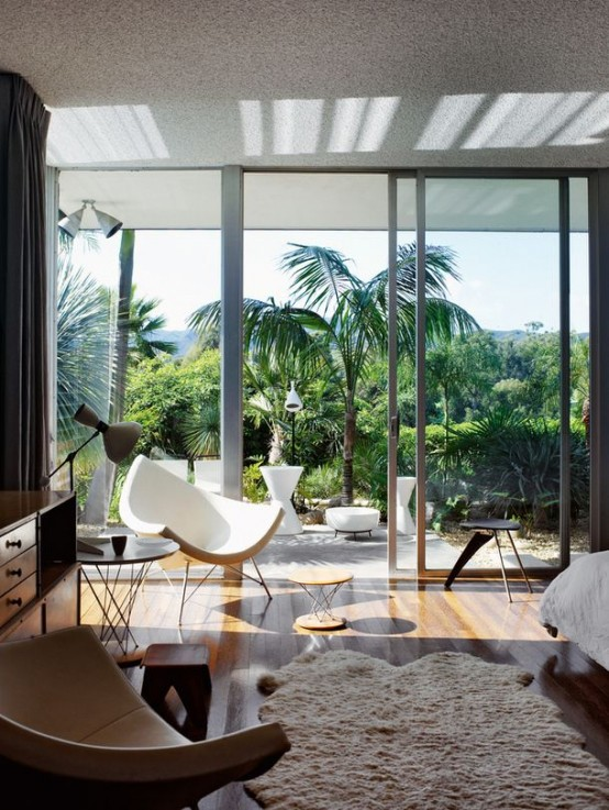 a tropical mid-century modern bedroom with stylish furniture and a glass wall that separates the room the garden and provides cool views