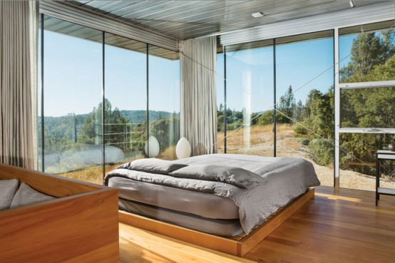 a stylish mid-century modern bedroom with glazed walls is centered around the views that inspire and look fantastic and curtains allow to make it private