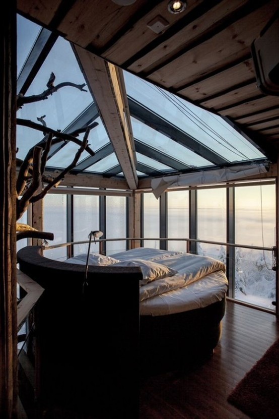 a relaxing and simple bedroom with a rounded bed, a glass ceiling and walls with a gorgeous winter view is amazing and very relaxing