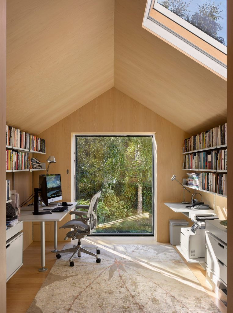 There's a home office with a large window and a skylight, with comfy furniture and open shelves