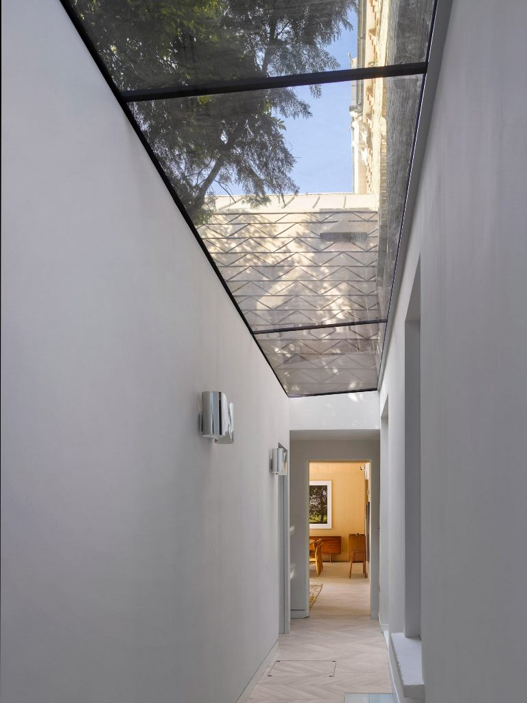 A glass-roofed corridor links the extension with the front of the house