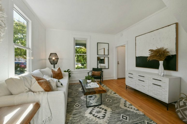 The living room features a monochromatic color scheme, chic furniture, a couple of mirrors and a boho rug