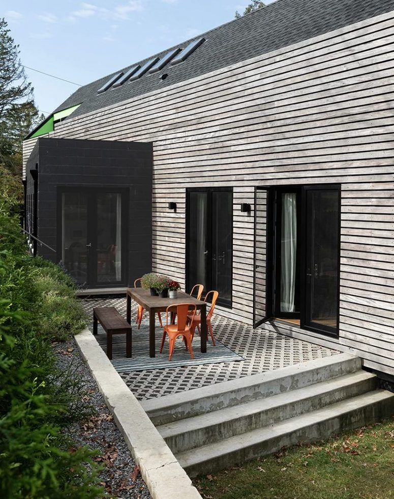 The exterior of the house is contrasting, dark and light, with a terrace with a wooden table and orange chairs