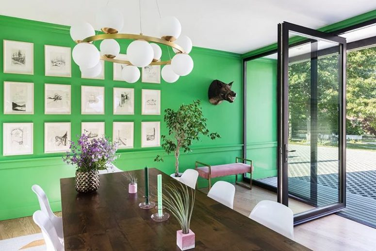 The dining room is done with a bold green wall, a pretty gallery wall, a wooden table and a pink bench