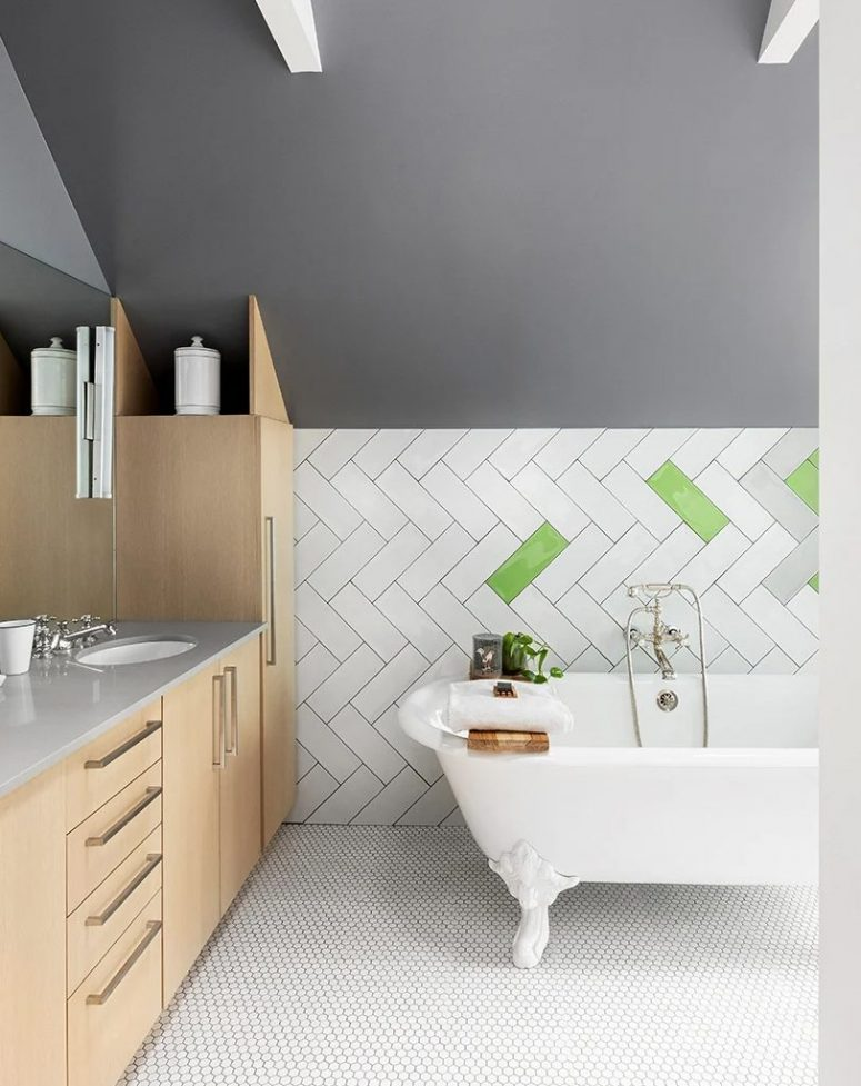 The bathroom is eye-catchy, with grey walls, boldly clad tiles, penny tiles on the floor, sleek plywood cabinetry and a vintage tub