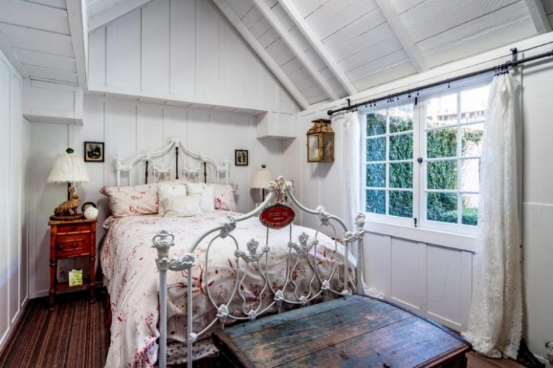 The bedroom is done with a metal bed, dark heavy furniture and floral bedding