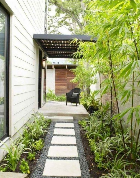 a low-maintenance front yard with pebbles, tiles, greenery and bamboo is a lovely idea for a modern home