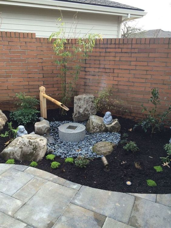 a small Japanese front yard with pebbles, greenery, a stone and bamboo fountain, rocks, shrubs is a lovely space