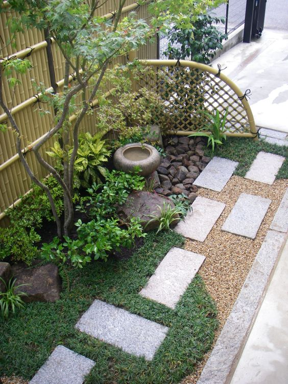 grass, concrete tiles, shrubs, a thin tree, a stoen bowl fountain and rocks for a lovely and chic Japanese-inspired look