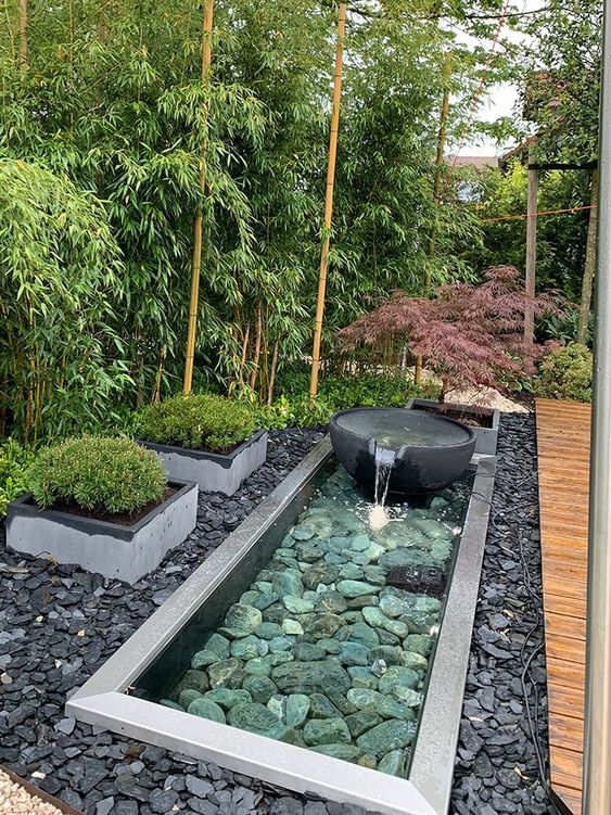 pebbles and rocks, a stone fountain, grasses in flower beds are amazing to complete a zen-like front yard