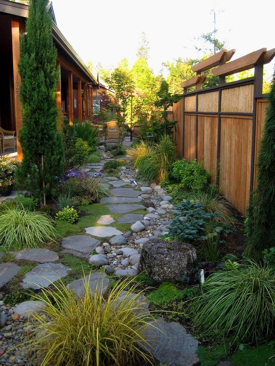 a Japanese-inspired garden with rock tiles, pebbles, tree stumps, greenery, grasses and a tall tree for a zen look