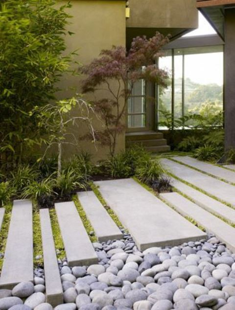 pebbles, long and narrow tiles, grass and mini Japanese trees at the entrance make the front yard very elegant, sleek and catchy