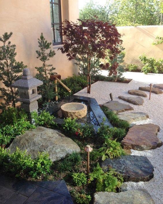 pebbles, rocks and rock tiles, a stone and bamboo fountain, greenery, a stone lantern and thin Japanese-style trees for a cozy feel