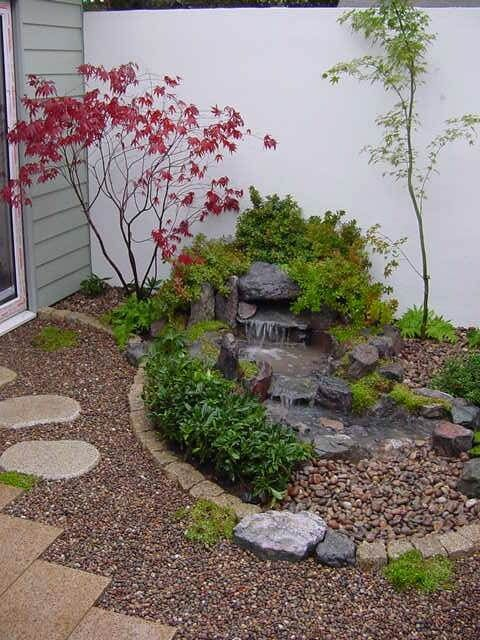 pebbles, tiles, a waterfall on rocks, shrubs and mini thin trees will make your outdoor space super inspiring and calming