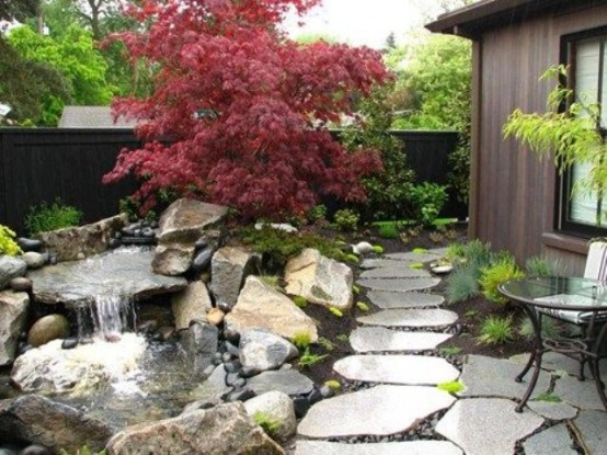 large rock tiles, greenery, moss, rocks and a waterfall and a red maple tree for a Japanese feel