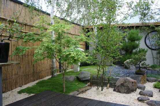 white pebbles, rocks, grass and thin trees plus a bamboo wall for a Japanese garden or front yard