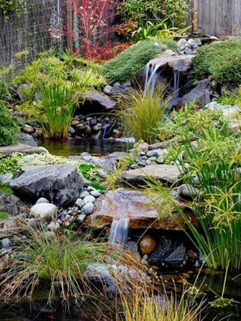 a chic Japanese front yard with waterfalls, rocks, pebbles, greenery and moss around for a relaxing and calming feel