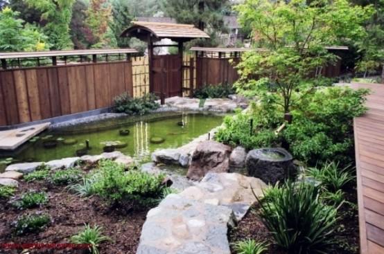 a Japanese garden with a pond, some shrubs and greenery and a couple of trees for a peaceful zen look